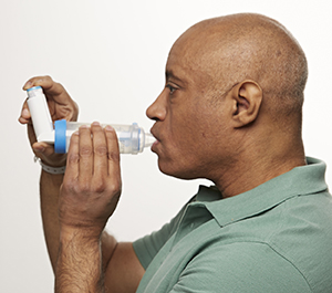 Man using metered-dose inhaler with spacer.